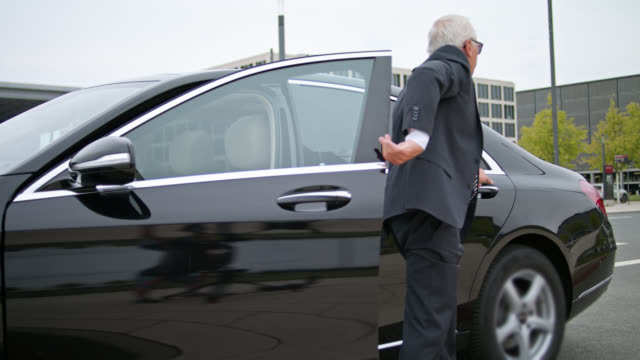 chauffeur opens back door of black limousine with discretion, senior vip businessman is exiting the car and in the end the car is driving off - car door stock videos & royalty-free footage