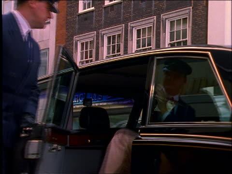 vídeos de stock e filmes b-roll de chauffeur opens car door as middle-aged couple get out / london - só homens maduros