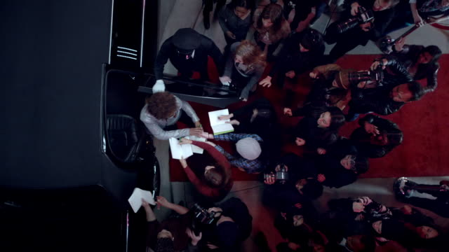 chauffeur opens limousine door, hip-hop artist signs autographs for fans at awards show - autogramm stock-videos und b-roll-filmmaterial