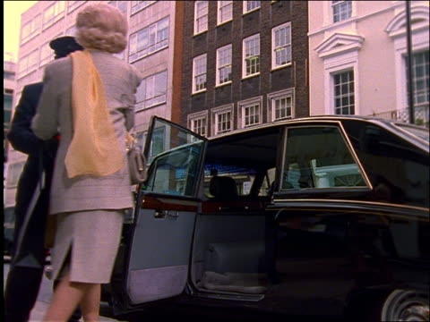 vídeos y material grabado en eventos de stock de chauffeur takes shopping bags from couple getting into car / london - 1990