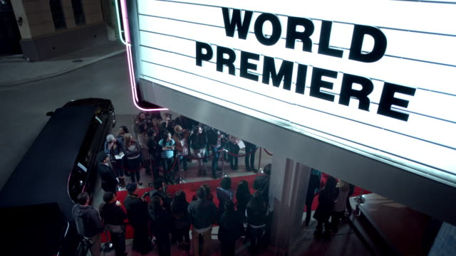 chauffeur waits by limousine under world premiere marquee at awards show - gala tilldragelse som firas bildbanksvideor och videomaterial från bakom kulisserna