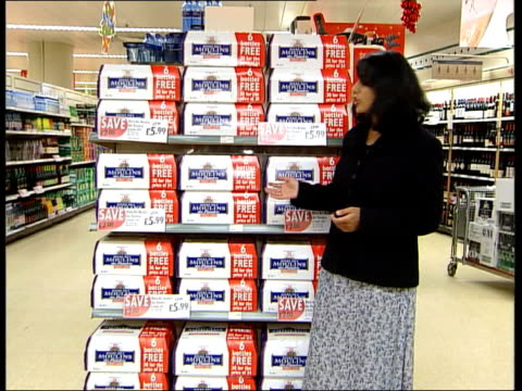 vídeos de stock e filmes b-roll de war on booze cruises itn england london sainsburys i/c shop assistant stacking boxes of french beer shopper pushing trolley thru alcohol section cms... - sainsburys