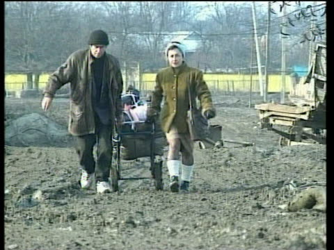 chechen couple pull pram piled with belongings along muddy road jan 00 - grosny stock-videos und b-roll-filmmaterial