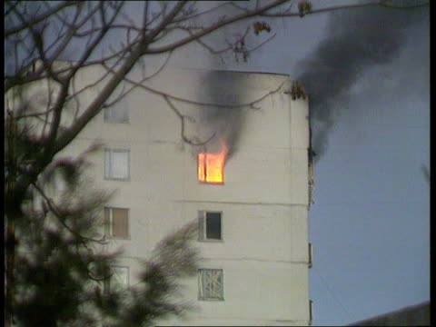chechnya - grozny about to fall; flames and smoke from top storey of building zoom in fierce flames leaping out of window fierce fire burning on... - grosny stock-videos und b-roll-filmmaterial
