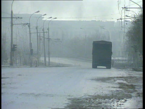 conflict chechnya grozny about to fall lorry away down empty road fast pan rl as explosion heard sot and smoke seen from ditto pull out ditto - grosny stock-videos und b-roll-filmmaterial