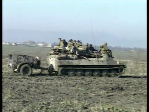 chechnya troops reported dead in grozny offensive lms armoured vehicles along armoured vehicle along pulling trailer pan helicopter gunship overhead... - grosny stock-videos und b-roll-filmmaterial