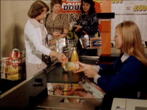 vídeos de stock e filmes b-roll de check out girl serving customer zoom in to hand running products over scanner introduction of bar codes; 25 july 79 - vendas