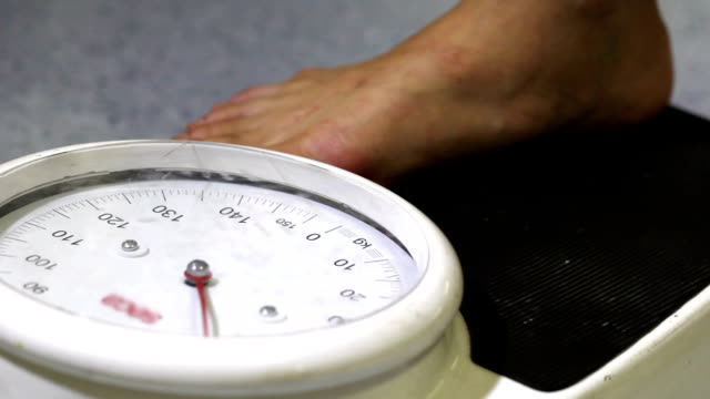 チェックの体重が体重計機 - 体重計点の映像素材/bロール