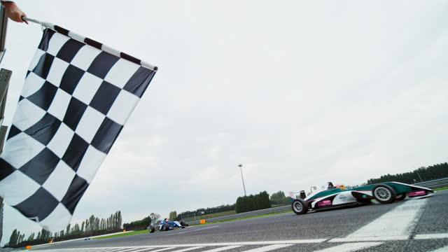 vídeos y material grabado en eventos de stock de slo mo checkered flag being waved in the formula race as the winner crosses the finish line - línea de meta