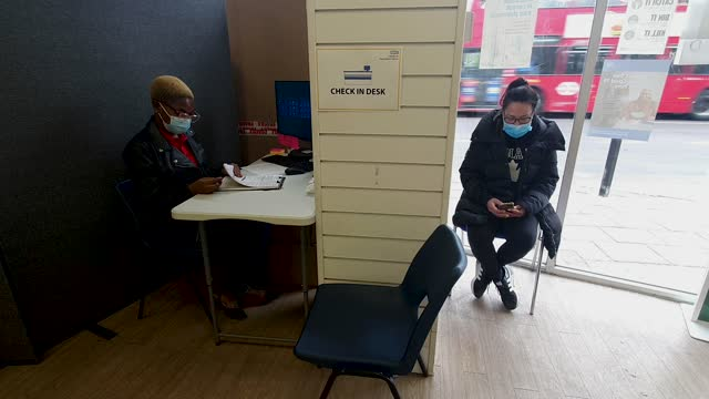 check-in receptionist yvette aa prekoh and a member of the public at the nhs vaccine centre at day lewis pharmacy, peckham high street, where the... - brian dayle coronavirus stock videos & royalty-free footage