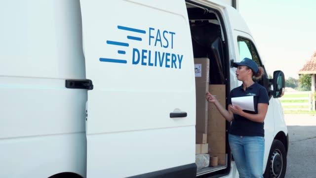 stockvideo's en b-roll-footage met een lijst met pakketten controleren - bestelwagen