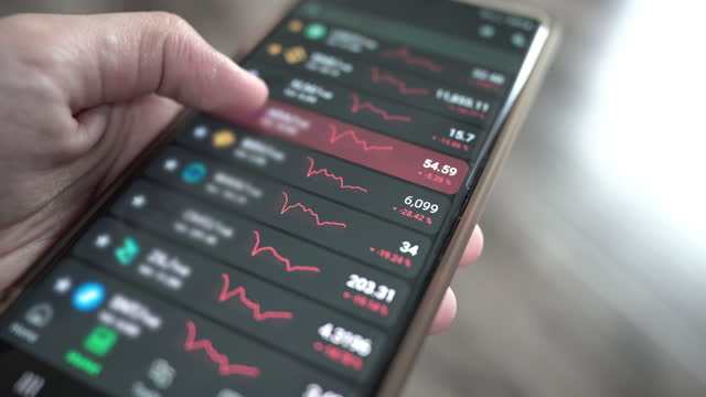 checking stock market or cryptocurrency data on mobile phone. - digital signage stock videos & royalty-free footage