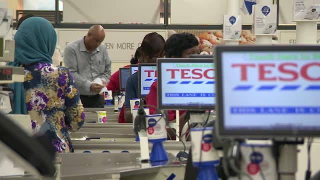 vídeos de stock e filmes b-roll de checkout at tesco extra supermarket in manchester - vendas