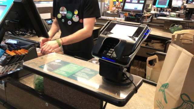 checkout at the amazon's whole foods grocery store in chattanooga, tennessee. amazon bought whole foods for $13.2 billion in 2017 and has over 500... - paper bag stock videos & royalty-free footage