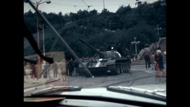 checkpoint at the height of the prague spring invasion car passes by tank - kampfpanzer stock-videos und b-roll-filmmaterial