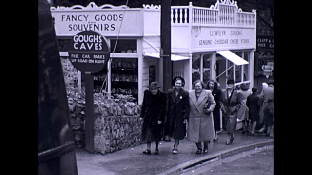 a group of people walk up past shops selling cheese and souvenirs / entrance to goughs caves / british 1930s standard flying 12 car - dna stock videos & royalty-free footage