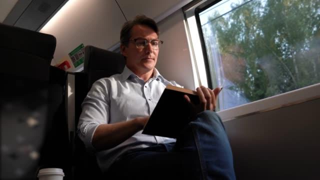 Vrolijke volwassen man woon-werkverkeer op de trein het lezen van een boek en genieten van het uitzicht