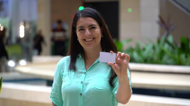 vidéos et rushes de femme adulte gai regardant l'appareil-photo souriant tout en tenant une carte pour éditer - carte de fidélité