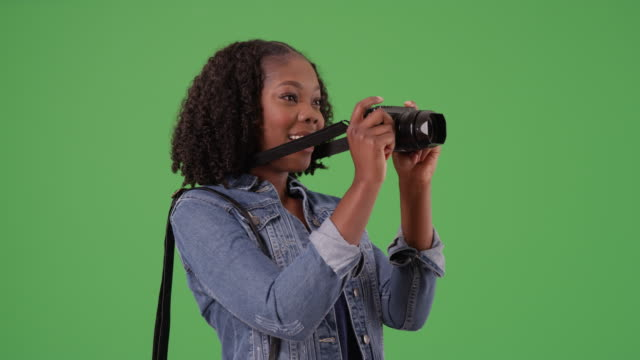 cheerful african american female snaps photo with camera on green screen - {{asset.href}} stock videos & royalty-free footage