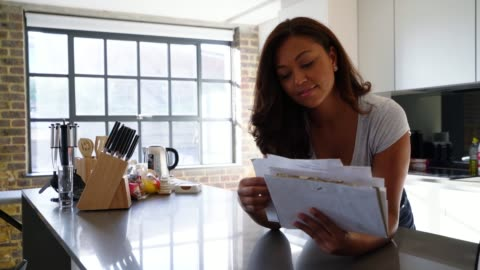 cheerful african american woman leaning on kitchen counter while checking her mail - letterbox stock videos & royalty-free footage