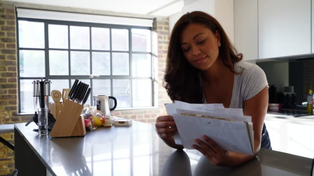vídeos de stock e filmes b-roll de cheerful african american woman leaning on kitchen counter while checking her mail - letterbox