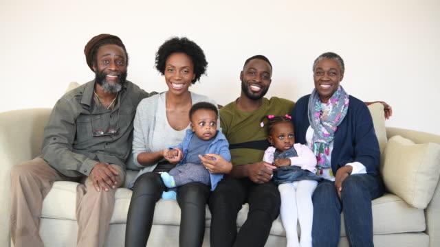 vídeos de stock, filmes e b-roll de família africana alegre sentados juntos e sorrindo para a câmera - unidade
