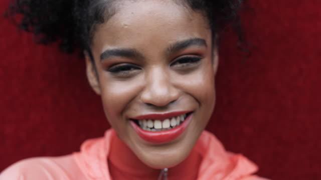 vidéos et rushes de cheerful african-american woman portrait, close up - fond coloré