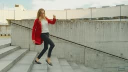 Cheerful and Happy Young Woman Actively Dancing While Walking Down the Stairs. She's Wearing a Long Red Coat. Scene Shot in an Urban Concrete Park Next to Business Center. Day is Bright.