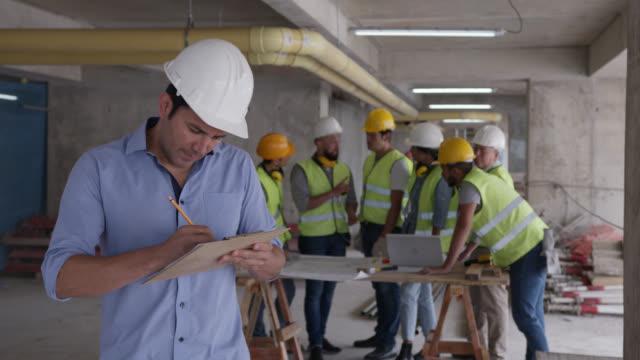 vídeos de stock, filmes e b-roll de arquiteto alegre em um canteiro de obras segurando uma prancheta e, em seguida, sorrindo para a câmera - protetor de ouvido