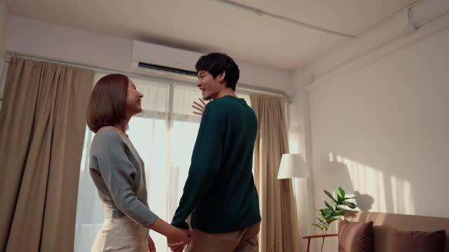 vidéos et rushes de main asiatique gaie de couples retenant et marchant dans leur nouvelle maison. - regarder autour de soi