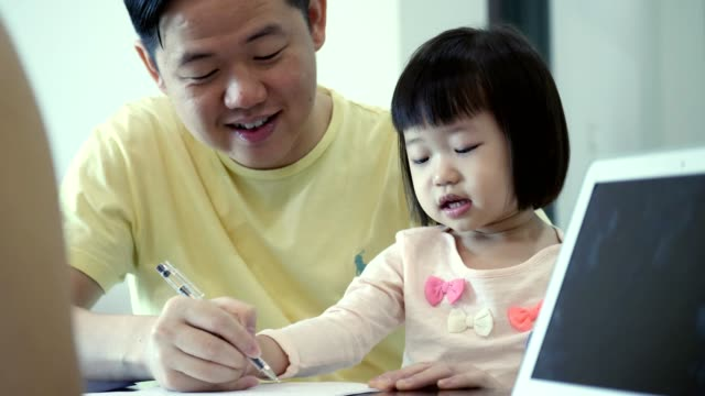 cheerful asian dad helps toddler daughter draw a picture - malay family stock videos and b-roll footage