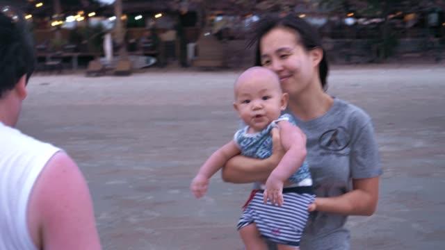 glad asiatisk familj lekfullt på stranden - 6 11 månader bildbanksvideor och videomaterial från bakom kulisserna