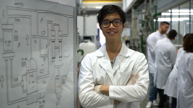 cheerful asian student during a laboratory standing next to the white board and facing camera smiling with arms crossed - post secondary education stock videos & royalty-free footage
