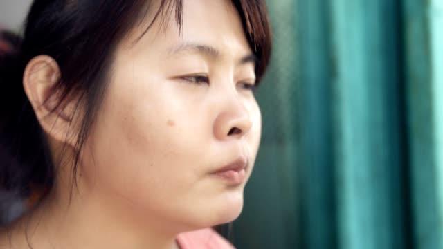 cheerful Asian woman eating dessert