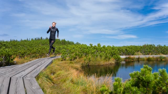 Fröhliche sportliche Frau läuft auf einem hölzernen Pfad unter Pinien Büschen an einem See an einem sonnigen Tag