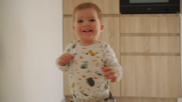 自宅で彼の最初のステップを作る陽気な男の子 - 男の赤ちゃん一人点の映像素材/bロール