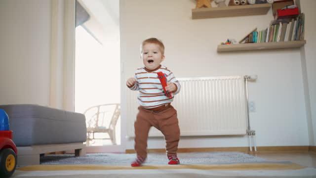 allegro bambino si alza e fa i suoi primi passi - stare in piedi video stock e b–roll