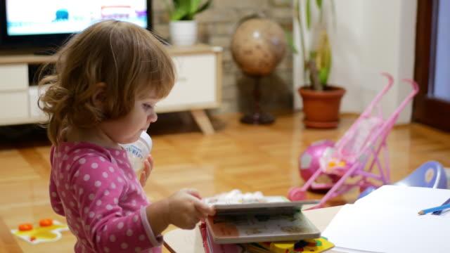 vídeos de stock e filmes b-roll de cheerful baby girl having fun at home and reading the book - soletrar
