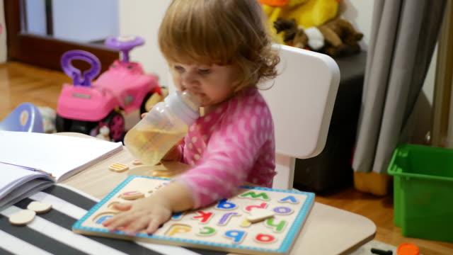 vídeos y material grabado en eventos de stock de niña alegre diversión en casa con juguetes y cartas - texto
