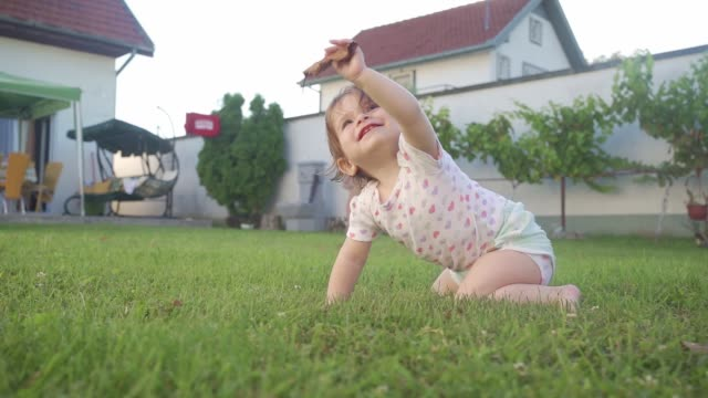 cheerful baby girl raising a fallen leaf while playing in the back yard - human limb stock videos & royalty-free footage