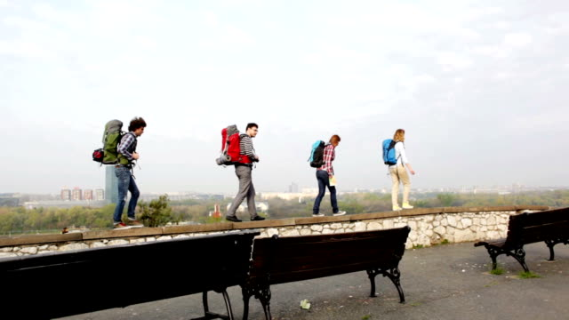 HD: Cheerful Backpackers Walking On The Wall.