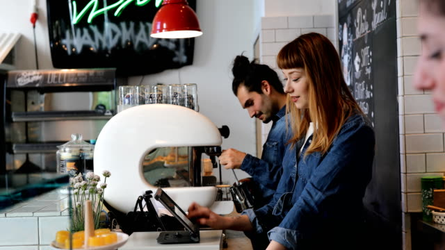 cheerful baristas working while talking at cafe - barista stock videos and b-roll footage