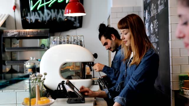 fröhliche baristas arbeiten während des gesprächs im cafe - café stock-videos und b-roll-filmmaterial