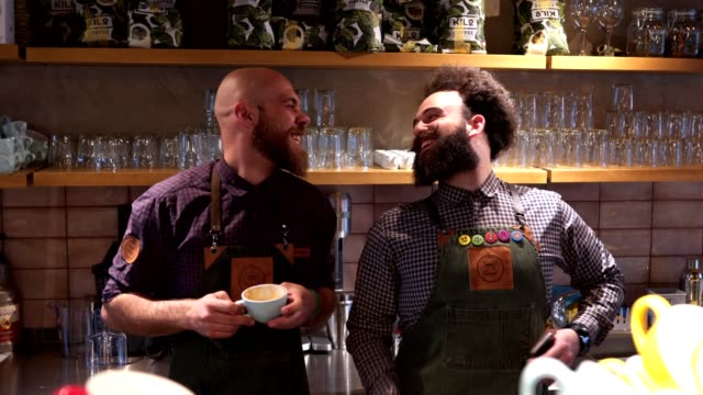 cheerful bearded coworkers enjoying coffee at a cafe - grembiule video stock e b–roll