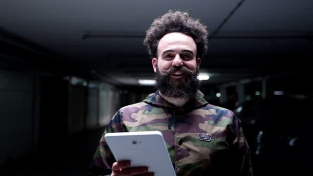 cheerful bearded entrepreneur holding a digital tablet - multi storey stock videos & royalty-free footage
