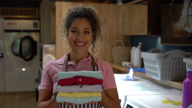 cheerful beautiful employee at a laundry service holding a stack of folded shirts while facing camera smiling - launderette stock videos & royalty-free footage