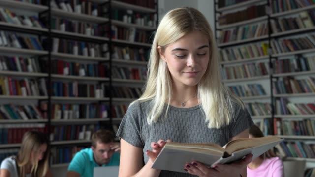 cheerful beautiful student reading a book slightly smiling - biblioteca video stock e b–roll