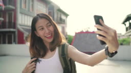 Cheerful beautiful young Asian backpacker blogger woman using smartphone taking selfie while traveling at Chinatown in Beijing, China. Lifestyle backpack tourist travel holiday concept.