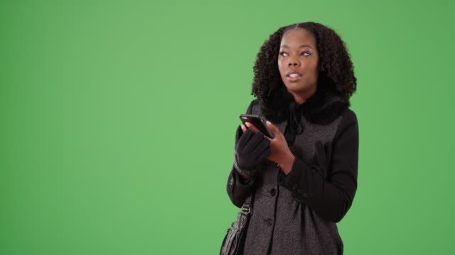 cheerful black female in winter coat waves to friend on greenscreen to be keyed - {{asset.href}} stock videos & royalty-free footage
