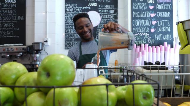 Fröhliche schwarzer Mann mit einem Saft in eine Flasche, die auf der Suche sehr glücklich und lächelnd